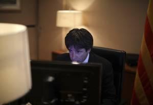Carles Puigdemont concentrado sobre seu discurso em sua mesa na sede do governo catalão Foto: Emilio Morenatti / AP