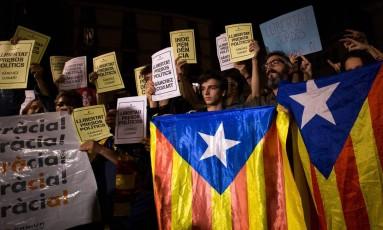 Catalães carregam bandeiras da Catalunha e cartazes com pedidos de liberdade para presos políticos em frente à sede do governo regional em Barcelona Foto: PAU BARRENA / AFP
