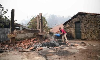 Mulher despeja água em local queimado em Vila Nova, próximo a Vouzela, em Portugal Foto: FRANCISCO LEONG / AFP