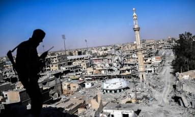 Silhueta de integrante das Forças Democráticas Sírias sobre prédio em Raqqa, na Síria Foto: BULENT KILIC / AFP