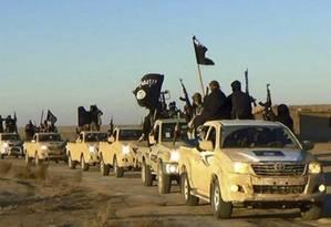 Em foto obtida e verificada pela AP em site militantes, combatentes do Estado Islâmico carregam armas e bandeiras do grupo extremista em comboio saindo de Raqqa para o Iraque Foto:  / AP