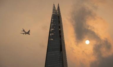 Avião sobrevoa céu de Londres, avermelhado pela junção da poeira dos incêndios de Portugal com os ventos da tempestade Ofélia Foto: Dominic Lipinski / AP