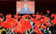 Estudantes erguem bandeiras chinesas enquanto assistem ao discurso de abertura do presidente Xi Jinping no XIX Congresso do Partido Comunista da China Foto: STR / AFP
