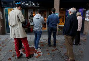 Catalães fazem fila para sacar dinheiro em protesto à saída de empresas da Catalunha Foto: GONZALO FUENTES / REUTERS