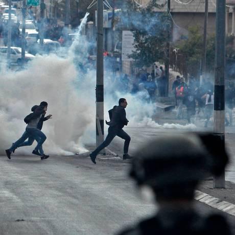 Manifestantes palestinos em meio à fumaça lançada por agentes das forças israelenses para dispersar protesto em Belém, na Cisjordânia Foto: MUSA AL SHAER / AFP