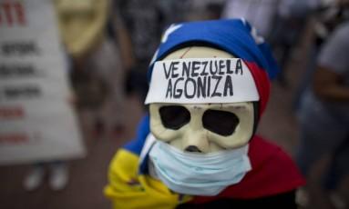 'Venezuela agoniza': diz máscara de manifestante em protesto contra a crise de saúde em Caracas Foto: Ariana Cubillos / AP