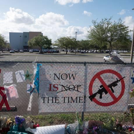 Mensagens de apoio e protesto contra armas na grade da escola Marjory Stoneman Douglas, alvo de massacre que deixou 17 mortos. Alunos e funcionários retornam ao local pela primeira vez desde o ataque armado Foto: STRINGER / REUTERS