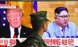 Soldado sul-coreano passa diante de televisão com imagens do presidente americano Donald Trump e o líder norte-coreano Kim Jong-un em estação de trem em Seul