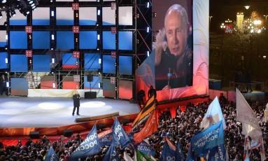Reeleito, presidente Vladimir Putin comemora diante de multidão em evento que celebrou o quatro aniversário de anexação da Crimeia à Rússia em Moscou Foto: ALEXEY NIKOLSKY / AFP