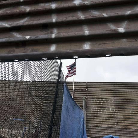 Bandeira dos EUA hasteada sobre cerca na divisa com o México na cidade mexicana de Tijuana Foto: GUILLERMO ARIAS / AFP