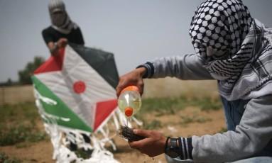 Palestinians preparam um acessório incendiário que será preso à pipa antes de lançá-la sobre a cerca na fronteira com Israel, nas imediações de Gaza Foto: AFP