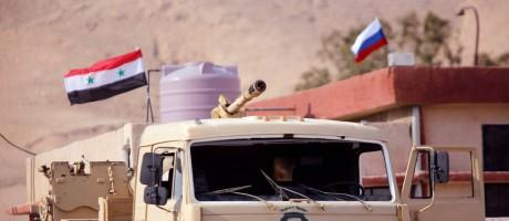 Veículo militar que pertencia aos rebeldes de Qalamoun oriental. Ao fundo, bandeiras síria e russa indicam a retomada da região Foto: OMAR SANADIKI / REUTERS