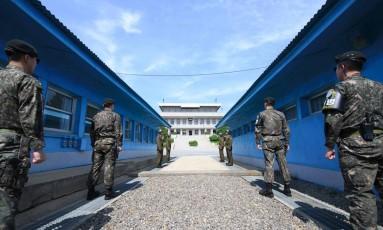 Soldados sul e norte-coreanos diante da linha de demarcação de concreto que divide as duas Coreias na vila de Panmumjom, na Zona Desmilitarizada Foto: - / AFP
