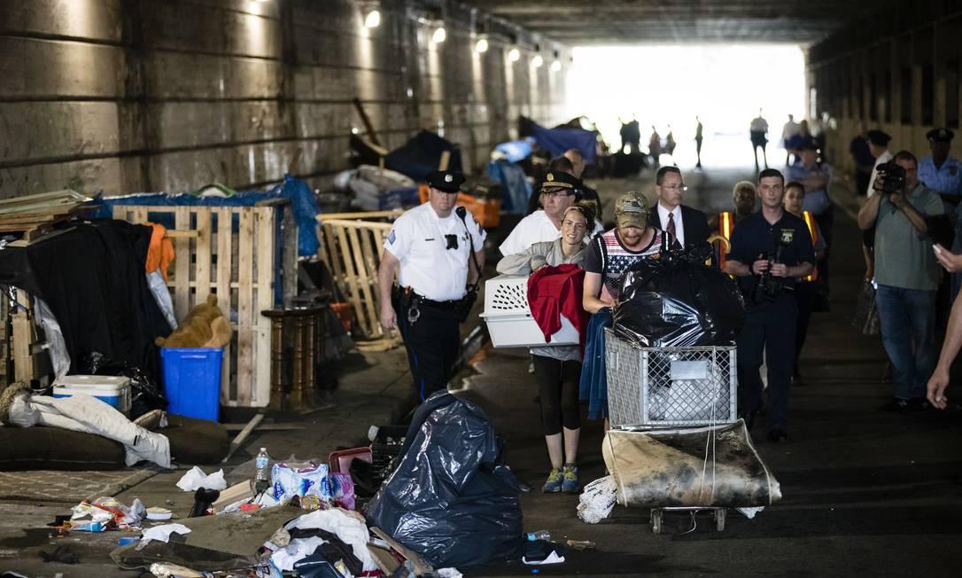 Policiais retiram moradores de rua que moram em acampamento irregular embaixo de ponte na Filadélfia, EUA Foto: Matt Rourke / AP