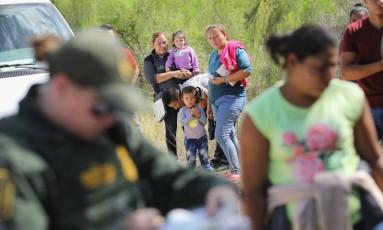 Agente de fronteira aborda migrantes na fronteira entre EUA e México, no Texas Foto: JOHN MOORE / AFP