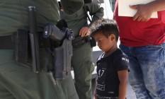 Pai e filho hondurenhos são abordados pela Patrulha Fronteiriça dos EUA perto de Mission, no Texas Foto: JOHN MOORE / AFP
