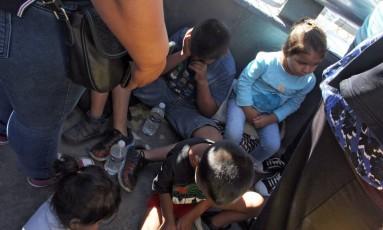 Crianças esperam na porta de entrada de Paso Del Norte, na fronteira com o México Foto: HERIKA MARTINEZ / AFP