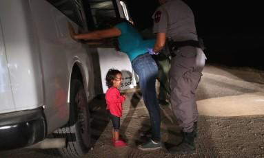 Menina hondurenha de quase 2 anos chora enquanto mãe é revista por agente de segurança americano, na fronteira entre México e Texas. As duas estão juntas em centro de detenção em McAllen, segundo o pai e governo de Honduras Foto: JOHN MOORE / AFP