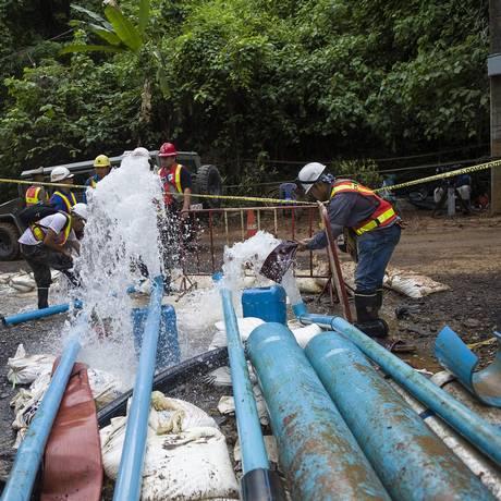 Equipe de emergência manuseia mangueira usada no sistema de drenagem de água instalado na caverna de Tham Luang no resgate dos 13 meninos presos, na Tailândia Foto: YE AUNG THU / AFP