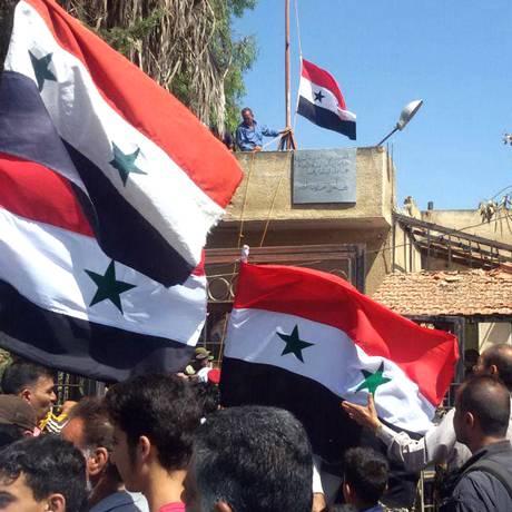 Sírios erguem bandeira nacional após forças do regime de Assad conquistarem a cidade de Tafas, em Deraa Foto: Sana / AFP