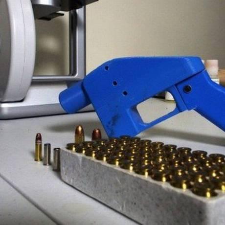 Uma pistola ao lado de uma impressora 3D Foto: ROBERT MACPHERSON / STF