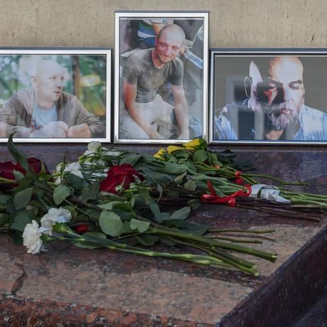 Flores diante de fotos dos jornalistas assassinados Alexander Rastorguyev, Kirill Radchenko e Orkhan Dzhemal, no Centro de Imprensa da República Centro-Africana Foto: VASILY MAXIMOV / AFP