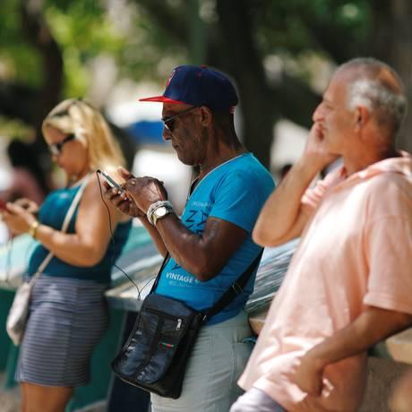 Cubanos checam a internet nos celulares, em Havana Foto: TOMAS BRAVO / REUTERS