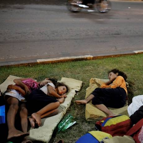 Imigrantes venezuelanos dormem em gramado em frente ao terminal de ônibus de Boa Vista, em Roraima, em meados de agosto Foto: NACHO DOCE / REUTERS