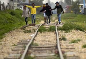 Imigrantes venezuelanos caminham em linha de trem em Bogotá, nos arredores de um acampamento improvisado Foto: RAUL ARBOLEDA / AFP