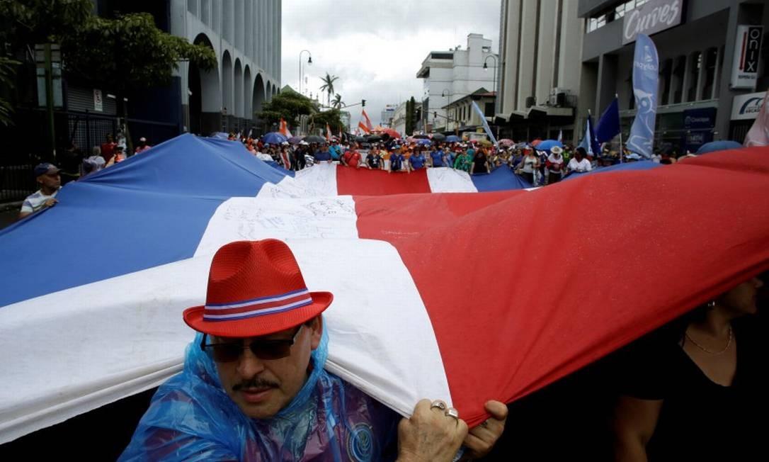 Funcionários públicos seguram da Costa Rica na greve que entra na quarta semana Foto: JUAN CARLOS ULATE / REUTERS