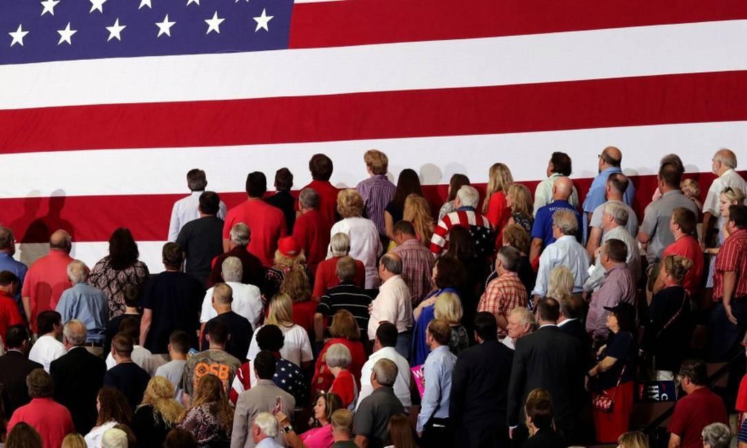 Pessoas voltadas para a bandeira americana durante um comício de Trump no Mississippi Foto: JONATHAN ERNST / REUTERS
