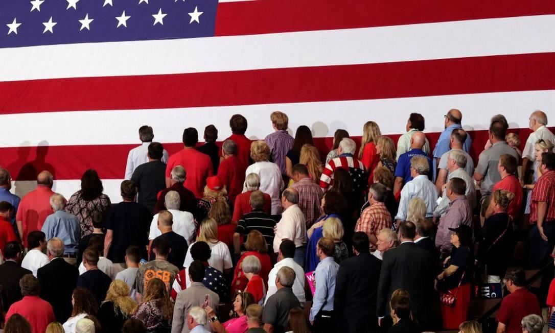 Pessoas viradas para a bandeira americana durante um comício de Trump no Mississipi Foto: JONATHAN ERNST / REUTERS