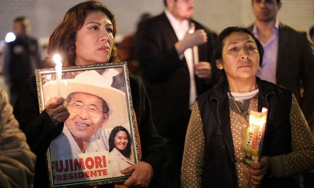 Pessoas seguram cartaz em apoio ao ex-presidente Alberto Fujimori em frente à clínica onde ele está internado em Lima Foto: LUKA GONZALES / AFP
