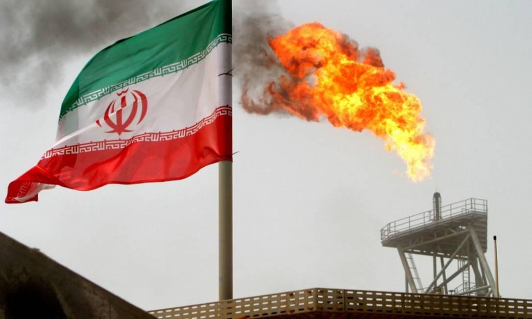 A bandeira iraniana tremula com uma chaminé ao fundo em uma plataforma de petróleo no Golfo Pérsico Foto: Raheb Homavandi / REUTERS