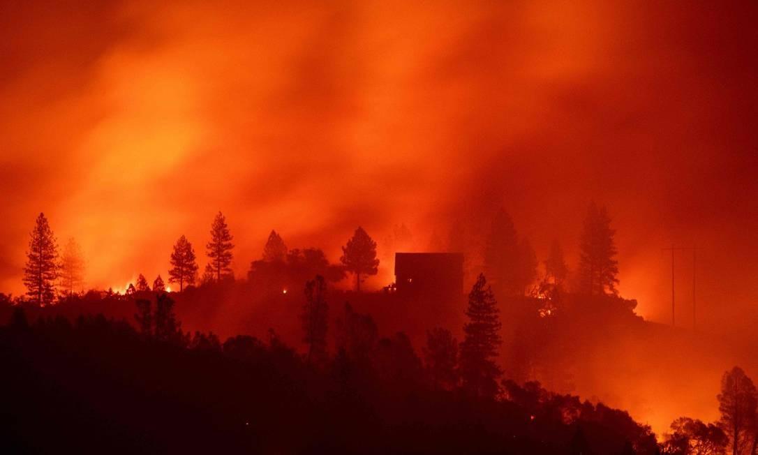 Casas no alto de colina são cercadas pelas chamas no incêndio Camp, no Norte da Califórnia Foto: JOSH EDELSON / AFP