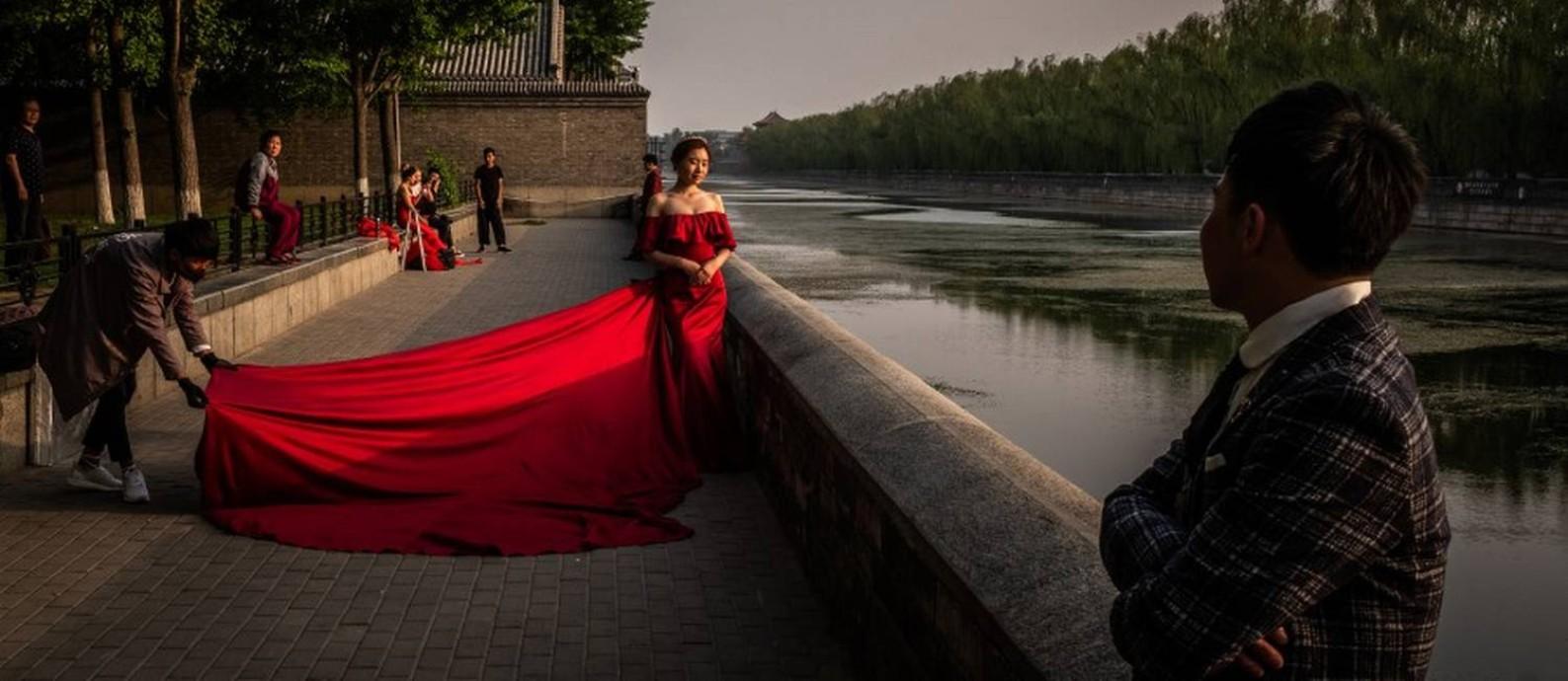 Uma noiva e um noivo posam para uma sessão de fotos nos arredores do parque Jingshan, em Pequim Foto: BRYAN DENTON / NYT