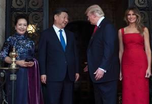 O presidente chinês Xi Jinping e sua mulher Peng Liyuan são recebidos por Donald e Melania Trump na Florida em abril de 2017 Foto: JIM WATSON / AFP