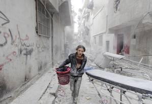 Um menino carrega seus pertencentes em uma área atingida por uma bomba que ativistas atribuem a forças do presidente sírio Bashar al-Assad em Aleppo Foto: REUTERS FILE PHOTO / REUTERS -2-04-2015