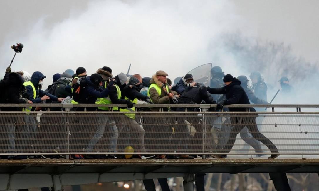 O ex-campeão francês de boxe Christophe Dettinger, de casaco e gorro pretos, se dirige a um policial caído ao lado de manifestantes Foto: GONZALO FUENTES / REUTERS