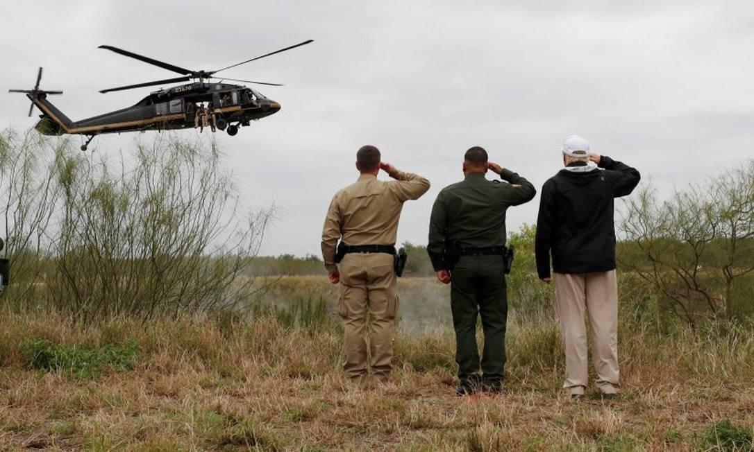 O presidente Donald Trump (à direita) faz saudação a agentes da patrulha americana em helicóptero na fronteira com o México Foto: LEAH MILLIS/REUTERS