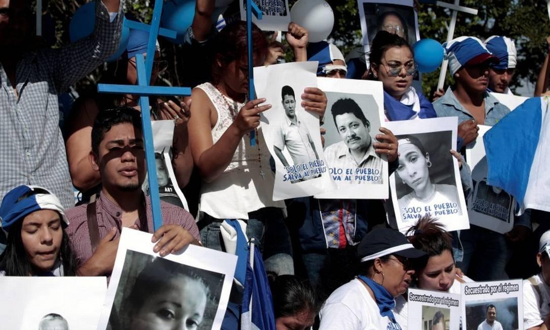 Nicareguenses vivendo na Costa Rico seguram cartazes de pessoas presas ou mortas em protestos contra o presidente Daniel Ortega Foto: JUAN CARLOS ULATE / Reuters