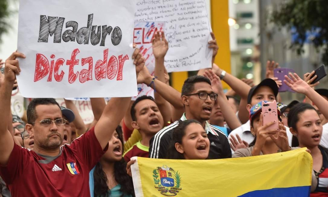 Venezuelanos que moram no Peru protestam em frente à embaixada de seu país em Lima Foto: CRIS BOURONCLE / AFP