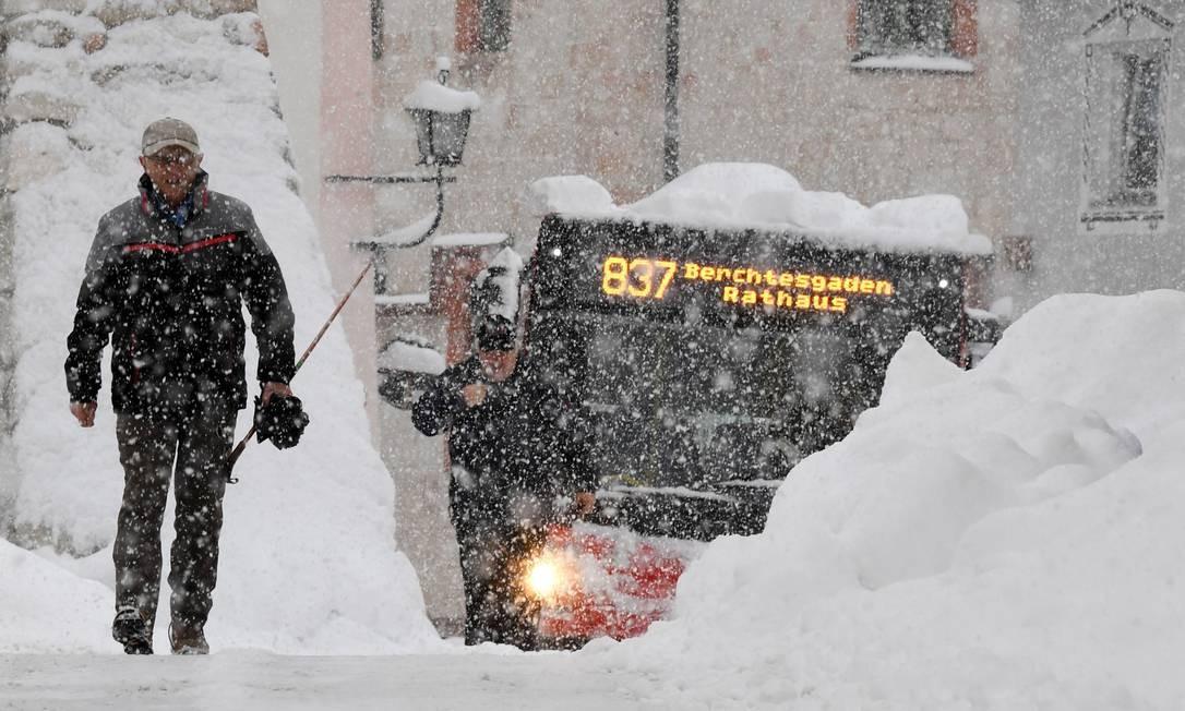Um homem e um ônibus dividem uma estrada coberta de neve em Berchtesgaden, no sul da Alemanha Foto: TOBIAS HASE / AFP