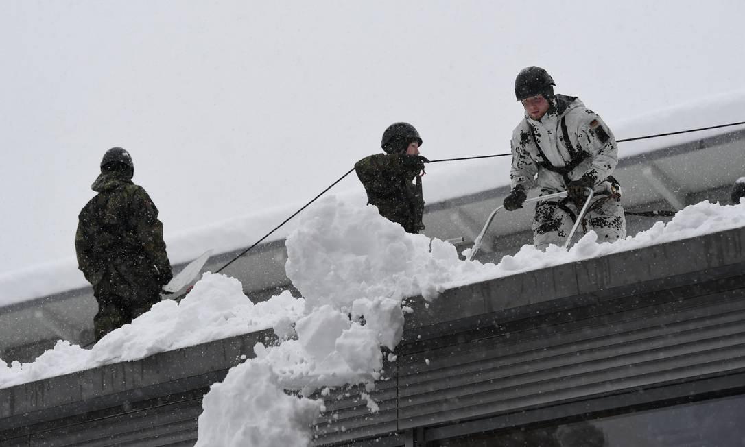 Soldados alemães removem neve do teto de uma escola ANDREAS GEBERT / REUTERS