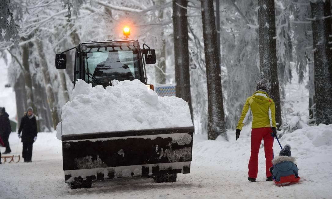 Uma mulher puxa uma criança em um trenó enquanto um trator carrega a neve para longe UWE ZUCCHI / AFP