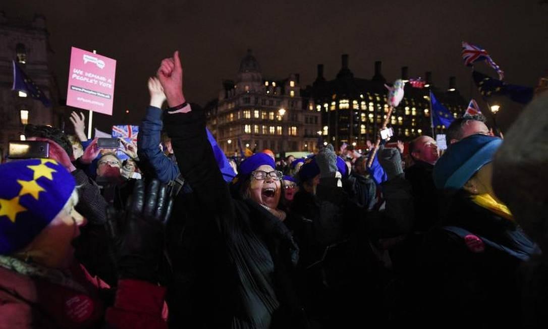 Do lado de fora do Parlamento britânico, resultado foi comemorado pelos manifestantes anti-Brexit Foto: OLI SCARFF / AFP