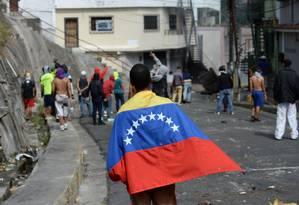 Um manifestante contra o governo camina com a bandeira venezuelana em confrontos entre policiais e manifestantes em Caracas Foto: FEDERICO PARRA / AFP