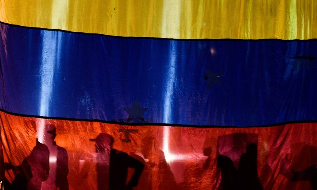 A sombra de ativistas é vista através em Caracas no dia 16 de janeiro Foto: FEDERICO PARRA / AFP