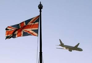 Aeronave da British Airways é fotografada ao fundo da bandeira do Reino Unido, hasteada no topo do Parlamento britânico, em 28 de janeiro de 2019 Foto: TOLGA AKMEN / AFP