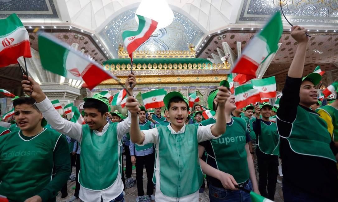 Milhares de pessoas se reuniram nesta sexta no mausoléu de Khomeini em Teerã. Usando coletes e bonés nas cores do país, parte delas formou uma bandeira iraniana. A revolução derrubou o xá Reza Pahlevi, que chegou ao poder em um golpe apoiado por americanos e ingleses que derrubou em 1953 o primeiro-ministro Mohammed Mossadegh; o premier havia nacionalizado o petróleo Foto: - / AFP